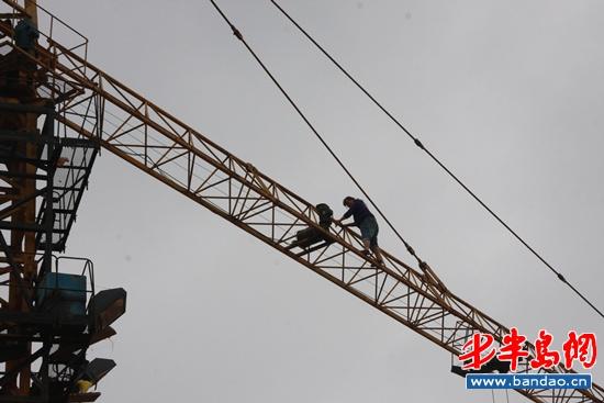 女子金某终于从塔吊的一端缓缓爬向塔吊驾驶室并安全回到地面.